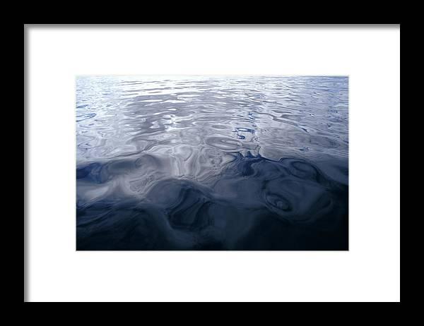Very Calm Ocean Framed Print featuring the photograph A Very Calm Ocean Reflects Grey-blue by Jason Edwards