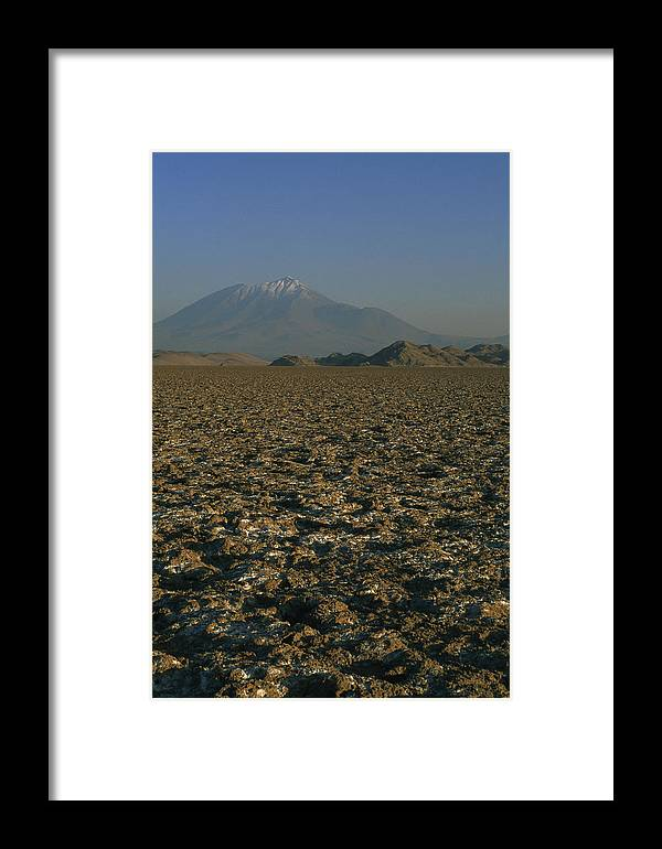 Altiplano Framed Print featuring the photograph A Volcano Rises Above A Dry Lake Bed by Gordon Wiltsie
