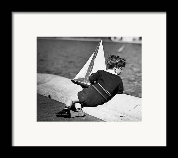 Child Framed Print featuring the photograph Boy Playing With Toy Sailboat by George Marks