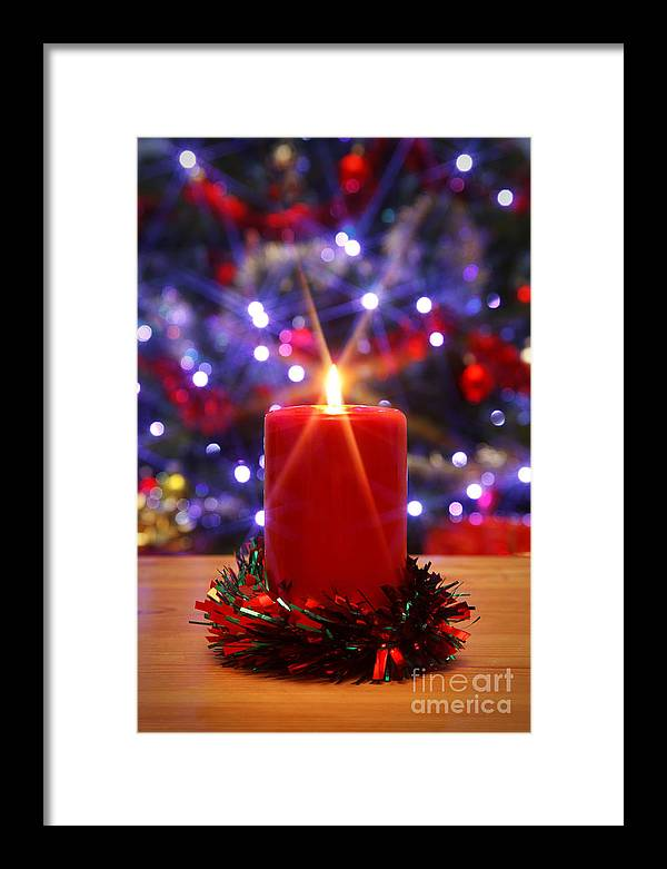 Christmas Framed Print featuring the photograph Christmas Candle With Starburst And Decorated Tree Background. by Richard Thomas