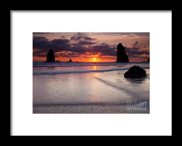 Cannon Beach Framed Print featuring the photograph Setting Between The Needles by Mike Dawson