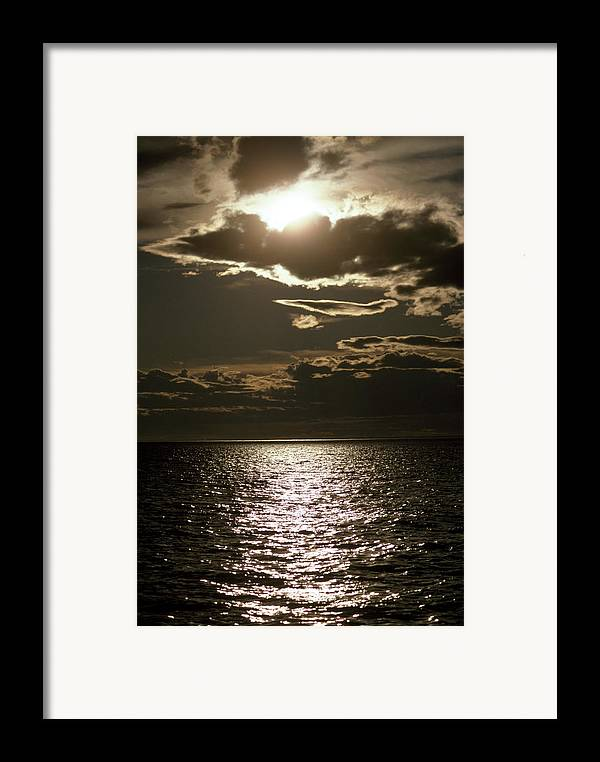 Outdoors Framed Print featuring the photograph The Setting Sun Pierces A Menacing by Jason Edwards