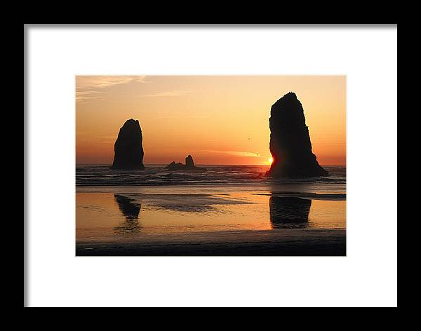 Cannon Beach Framed Print featuring the photograph The Sun Sets Over The Sea Stacks by Phil Schermeister