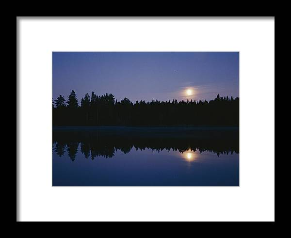 Scenic Views Framed Print featuring the photograph Trees And Sun Are Reflected In A Lake by Mattias Klum