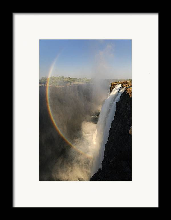 Rainbow At The Victoria Falls Framed Print featuring the photograph Victoria Falls by Christian Heeb