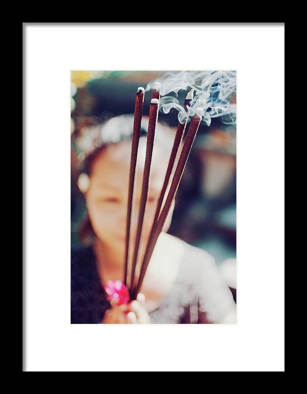 30's Framed Print featuring the photograph Beautiful Asian Woman Holding Incense Sticks During Hindu Ceremony In Bali, Indonesia by Srdjan Kirtic