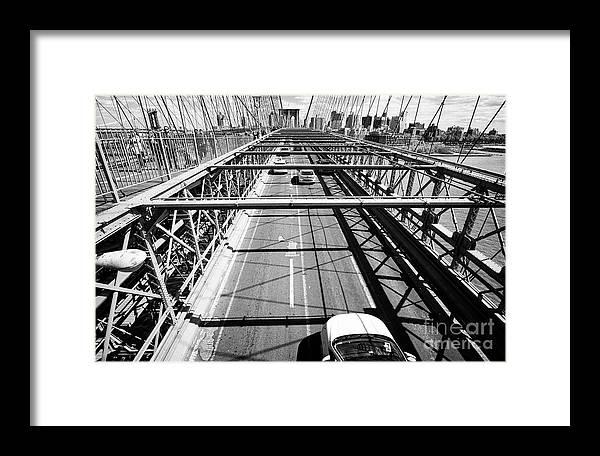 Brooklyn Framed Print featuring the photograph traffic vehicles driving over the worn tarmac on brooklyn bridge New York City USA by Joe Fox