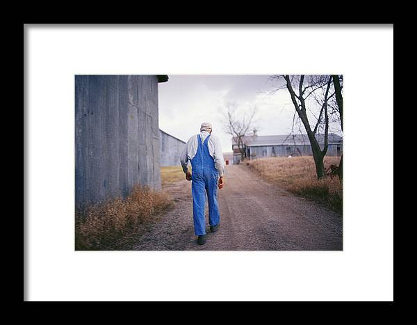 Scenes And Views Framed Print featuring the photograph An Elderly Farmer In Overalls Walks by Joel Sartore