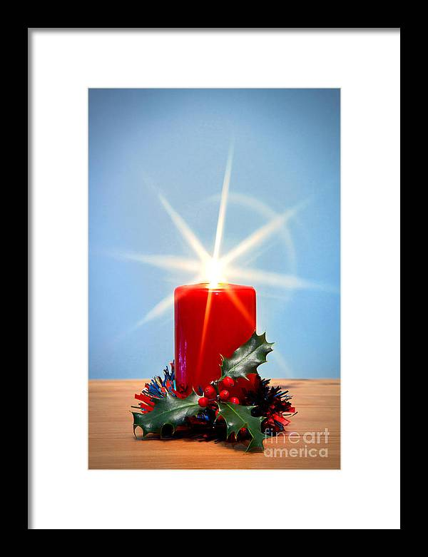 Christmas Framed Print featuring the photograph Christmas Candle With Starburst And Holly. by Richard Thomas