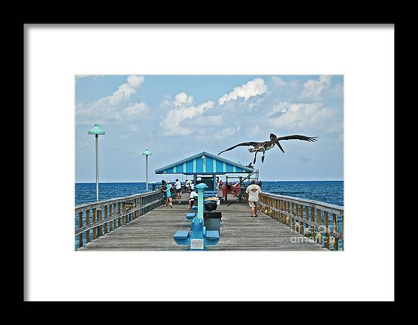 Fishing Pier Framed Print featuring the photograph Fishing Pier With Flying Pelican by Allan Einhorn