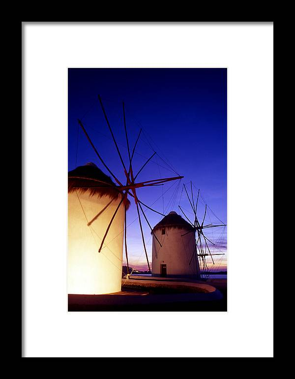 Architecture; Architectural; Cyclades; Mykonos Framed Print featuring the photograph Greece. Mykonos Town. Illuminated Windmills At Dusk. by Steve Outram
