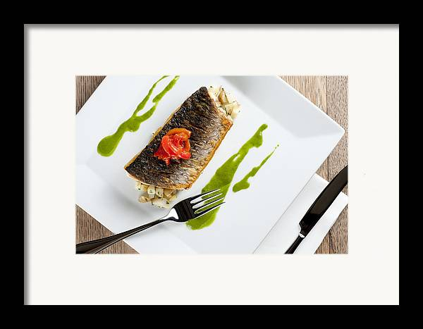 Grey Mullet Framed Print featuring the photograph Grey Mullet With Watercress Sauce Presented On A Square White Plate With Cutlery And Napkin by Andy Smy
