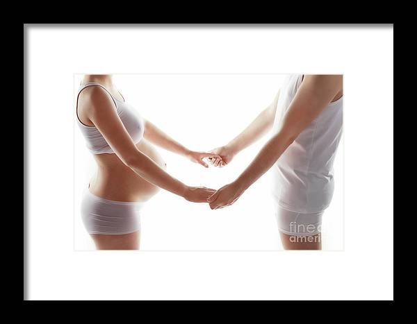 Pregnant Framed Print featuring the photograph Pregnant Woman Holding Hands With A Man. by Michal Bednarek