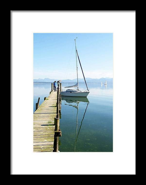 Chiemsee Framed Print featuring the photograph Sailing Boat And Reflection By Lake Pier by Jirawat Cheepsumol