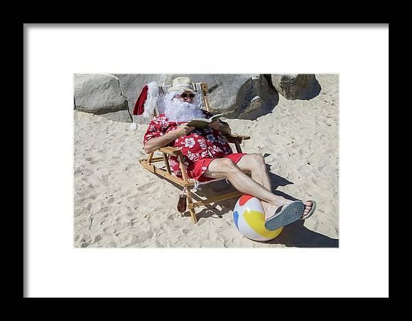 cedfe815 Beach Framed Print featuring the photograph Santa Claus Reading Novel On  Sunny Beach by Karen Foley