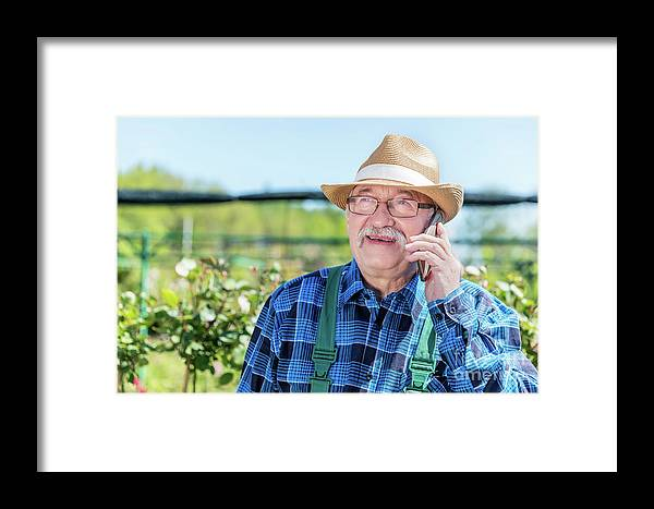 Garden Framed Print featuring the photograph Senior Gardener Talking On The Phone With A Client. by Michal Bednarek