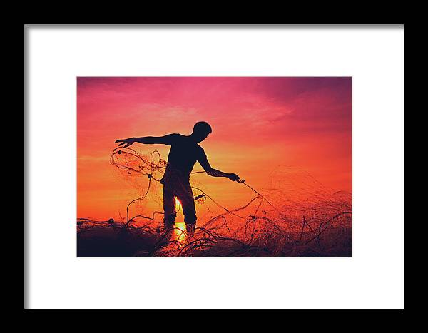 Active Framed Print featuring the photograph Silhouette Of A Local Fisherman Collecting His Nets On The Beach At The Sunset On Koh Lanta Island by Srdjan Kirtic