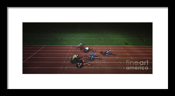14-15 Years Framed Print featuring the photograph Paraplegic Athletes Racing Along Sports Track In Night by Caia Image/science Photo Library