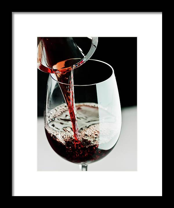 Alcohol Framed Print featuring the photograph Red Wine Being Poured In A Glass by Juanmonino