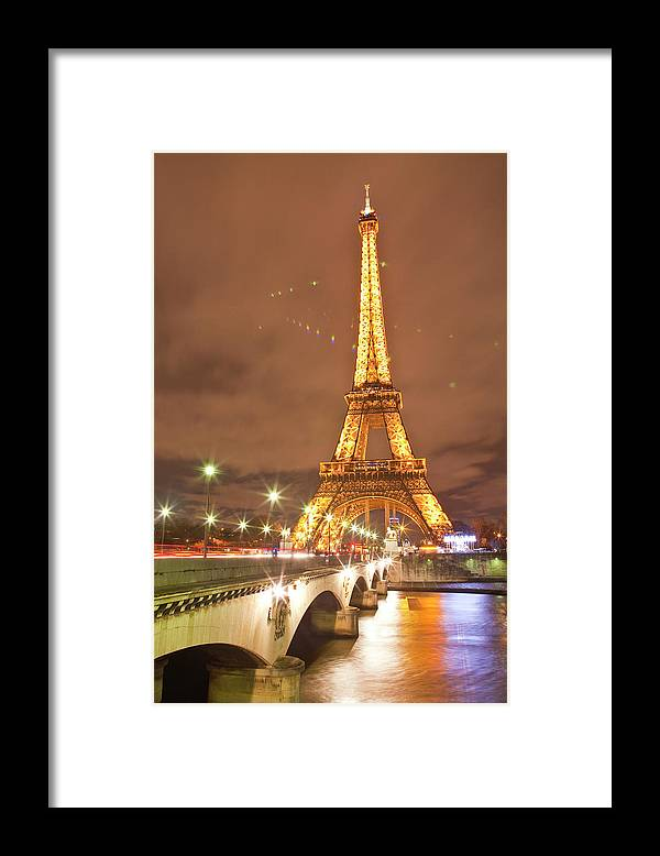 In A Row Framed Print featuring the photograph The Eiffel Tower Lit Up At Night In by Julian Elliott Photography