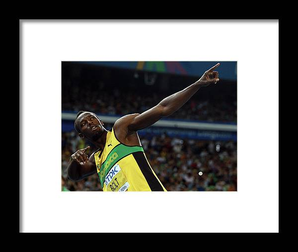 Usain Bolt 'to Di World' Pose Framed Print featuring the photograph 13th Iaaf World Athletics Championships by Alexander Hassenstein
