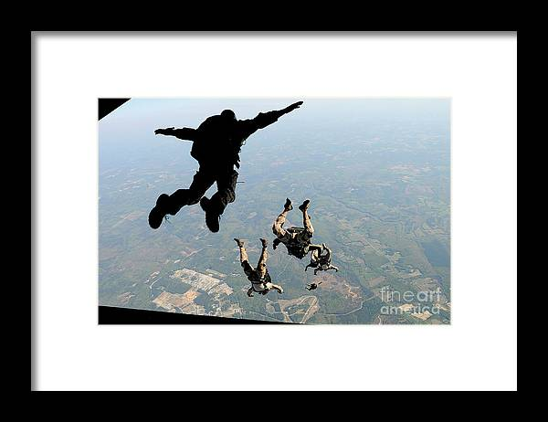 People Framed Print featuring the photograph Navy Seals Jump From The Ramp Of A C-17 by Stocktrek Images