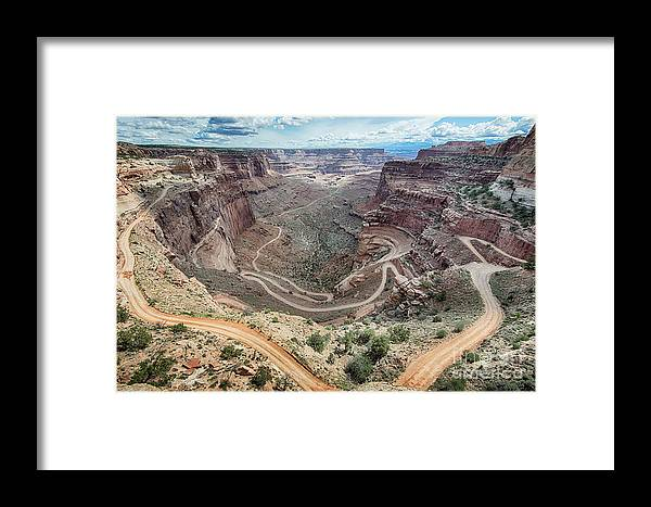Southwest Framed Print featuring the photograph A 4wd Vehicle Makes Its Way Down A Dirt by Steve Lagreca