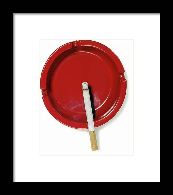 White Background Framed Print featuring the photograph A Red Ashtray With A Burning Cigarette by Steve Wisbauer