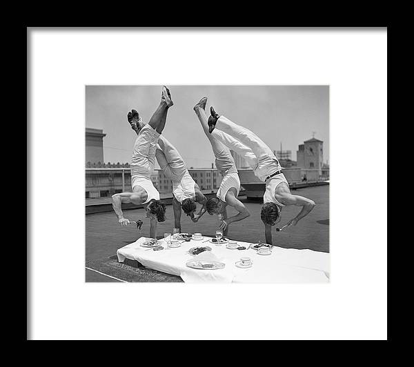 People Framed Print featuring the photograph Acrobats Eat While Doing Handstands by Bettmann