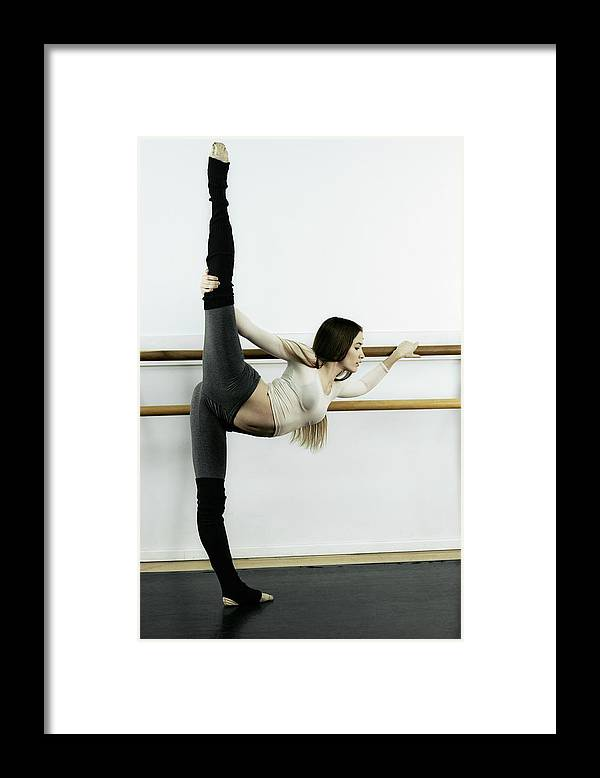 Ballet Dancer Framed Print featuring the photograph Ballet Dancer Stretching In Dance by Patrik Giardino