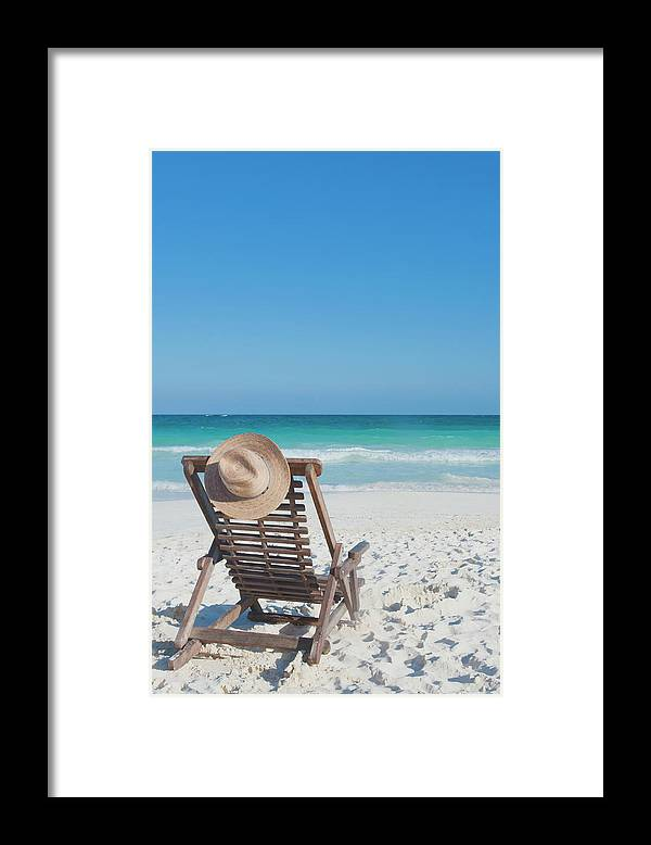 Scenics Framed Print featuring the photograph Beach Chair With A Hat On An Empty Beach by Sasha Weleber