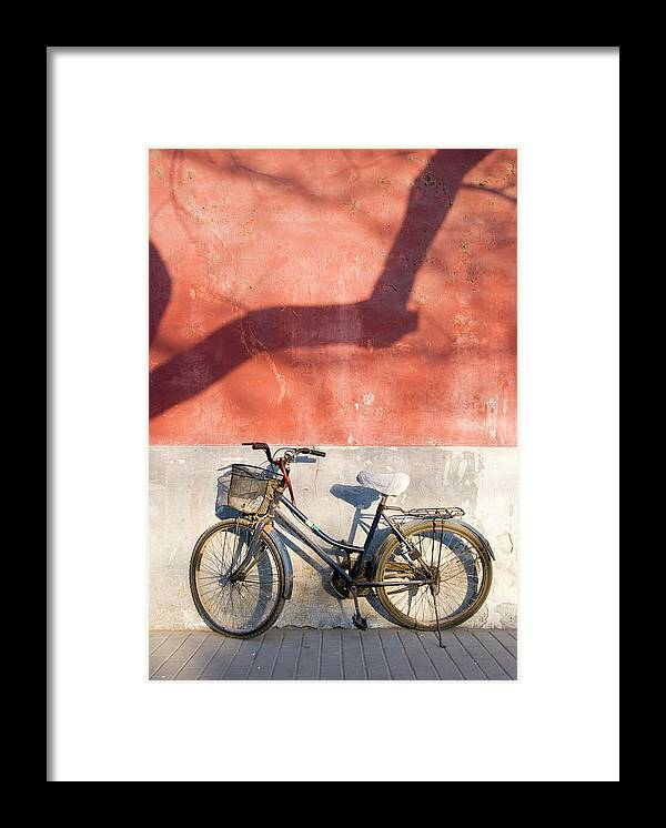 Chinese Culture Framed Print featuring the photograph Bicycle Against Red Wall by Frankvandenbergh