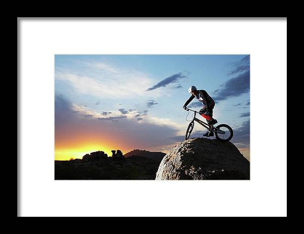 Sports Helmet Framed Print featuring the photograph Bike Rider Balancing On Rock Boulder by Thomas Northcut