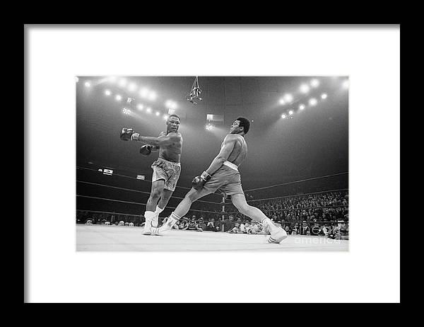 Joe Frazier Framed Print featuring the photograph Boxer Ali Dodging A Punch From Frazier by Bettmann