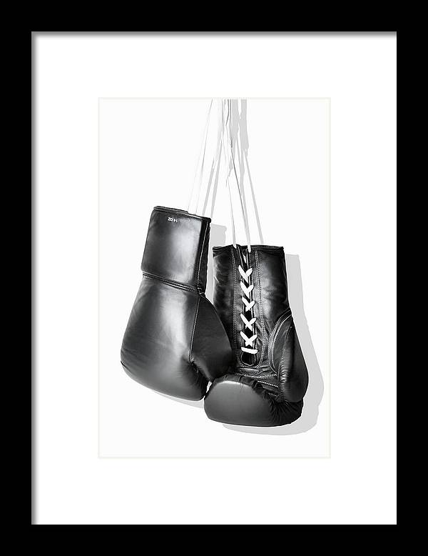 Hanging Framed Print featuring the photograph Boxing Gloves Hanging Against White by Burazin