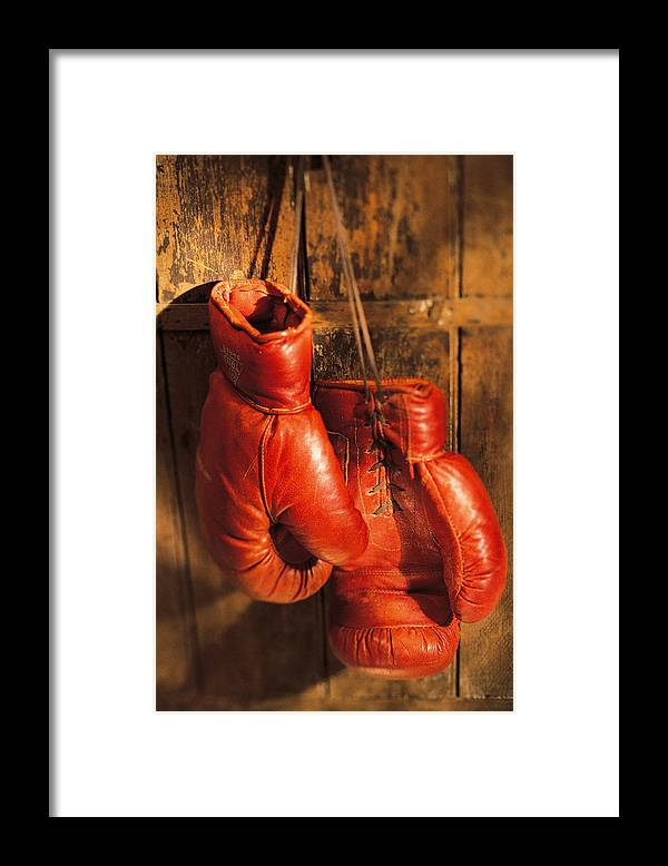 Hanging Framed Print featuring the photograph Boxing Gloves Hanging On Rustic Wooden by Comstock