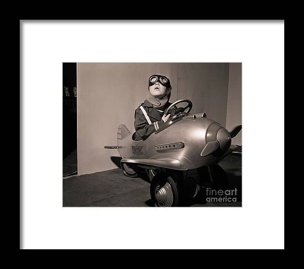 Child Framed Print featuring the photograph Boy In Aviator Suit Sitting In Toy Plane by Bettmann