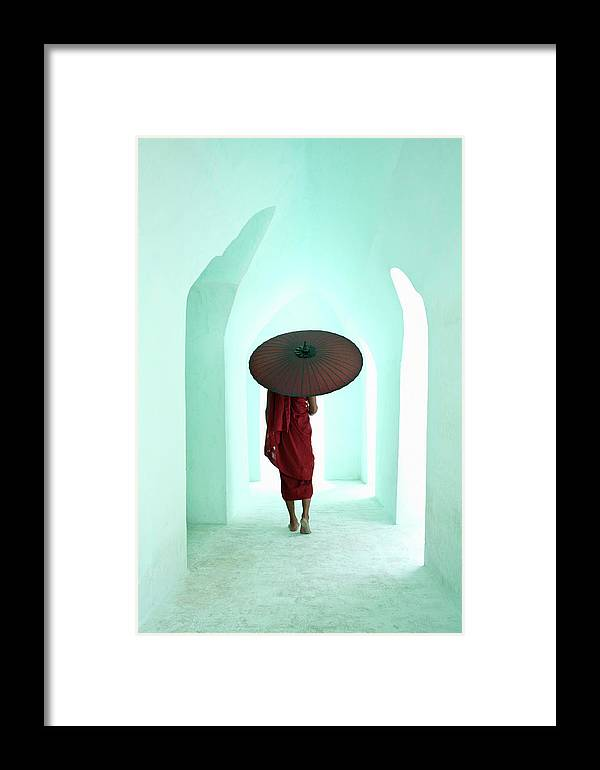 Arch Framed Print featuring the photograph Buddhist Monk Walking Along Arched by Martin Puddy