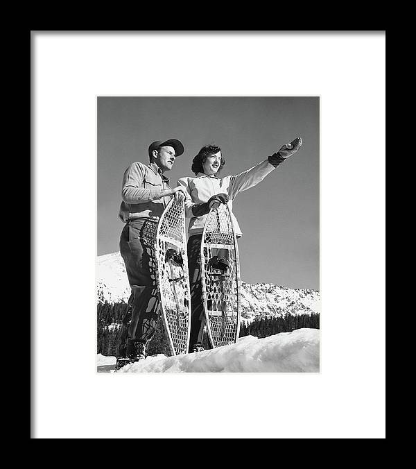 Heterosexual Couple Framed Print featuring the photograph Couple Holding Snowshoes, Woman Pointing by Stockbyte