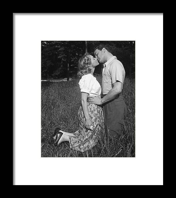 Heterosexual Couple Framed Print featuring the photograph Couple Kissing Outdoors by George Marks