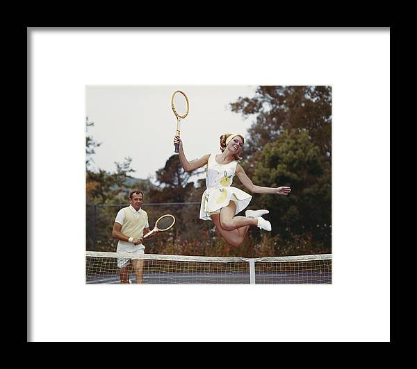 Heterosexual Couple Framed Print featuring the photograph Couple On Tennis Court, Woman Jumping by Tom Kelley Archive
