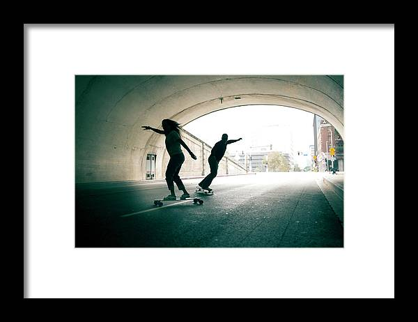 Mature Adult Framed Print featuring the photograph Couple Skateboarding Through Tunnel by Ian Logan