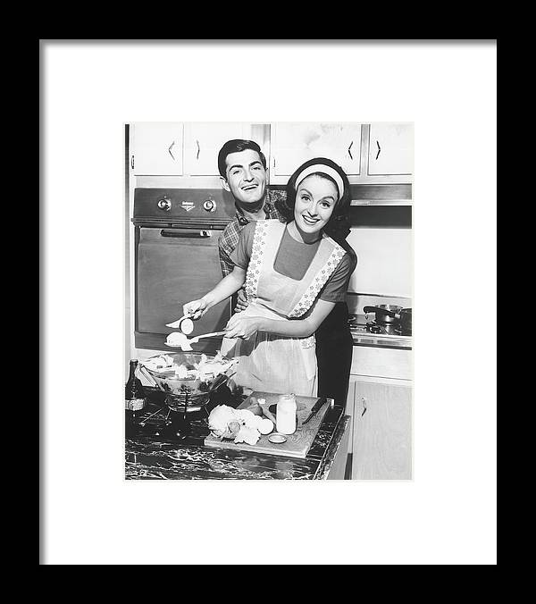 Heterosexual Couple Framed Print featuring the photograph Couple Standing In Kitchen, Smiling, B&w by George Marks