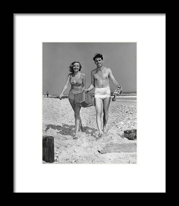 Heterosexual Couple Framed Print featuring the photograph Couple Walking With Picnic Basket On by George Marks