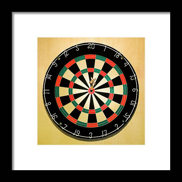 Expertise Framed Print featuring the photograph Dart In Bulls Eye On Dart Board by Fuse