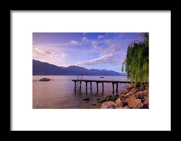 Tranquility Framed Print featuring the photograph Dock And Boat On Lake, Lago Di Garda by Radius Images