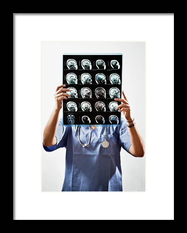 Expertise Framed Print featuring the photograph Female Doctor Holds Up Mri In Front Of by Ron Levine
