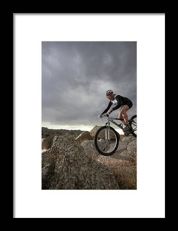 Sports Helmet Framed Print featuring the photograph Female Rider Mountain Biking Between by Thomas Northcut