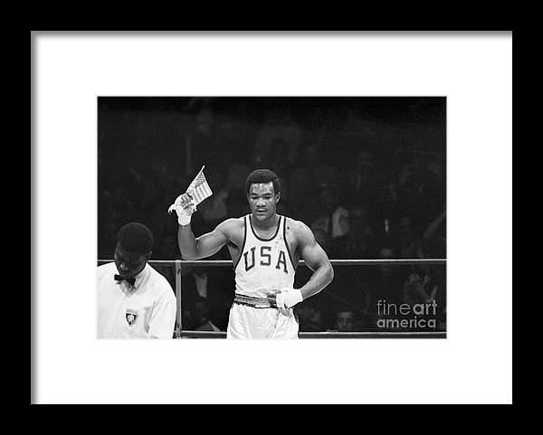 Young Men Framed Print featuring the photograph George Foreman Waves Us Flag At Olympic by Bettmann