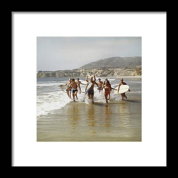 Young Men Framed Print featuring the photograph Group Of Surfers Running In Water With by Tom Kelley Archive